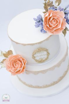Gold and white cake with peach-coloured roses, gold leaves and lilac freesias.