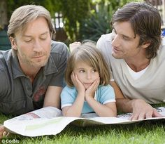 gay couples | gay couple reads with their adopted daughter.