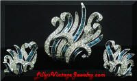 """BOUCHER Flowing Blue Clear Rhinestones Brooch Earrings Set  The design is a flowing sea grass.  This set has the quality and style of many Boucher pieces.  Gorgeous sapphire blue baguettes and clear chaton rhinestones are pave set in rhodium silver tone.  The brooch measures approx. 2"""" x 2"""".  The earrings are clip-on and measures approx. 1"""" x 1-1/4"""".  This set is in gorgeous vintage condition.  Reference: Brooch seen in  ABC's of Costume Jewelry by Salsbery, page 130.  #529083      $145.00"""