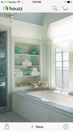 stenen blad om bad. Bad onder raam en lichtblauw met witte badkamer.