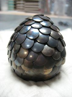 """dragon egg - Tacks that have been """"flamed"""" for color, pushed into a wooden egg."""