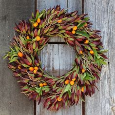 Crimson Citrus Wreath with red and green leucadendron leaves, stems of canary date palm fruit, bright orange kumquats, and citrus foliage - Flora Grubb Gardens