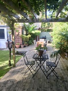 Wisteria & grape vine covered pergola with silver decking area & IKEA chair / table set