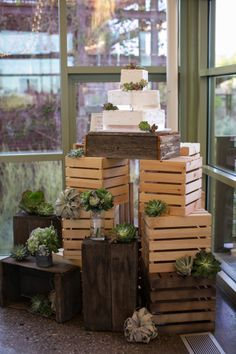 Cake display created out of crates and succulent embellishments. Springs Preserve industrial organic inspired wedding designed by Scheme Events. Florals by Layers of Lovely. Photography by Meg Ruth Photography. Paper Goods by She Paperie. Lighting by LED Unplugged. Las Vegas Wedding.