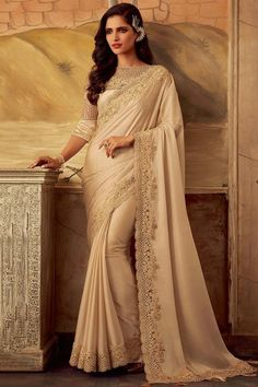 Cream Silk Saree with Cream Banglori silk blouse, embellished with dori work, resham work, sequins and stone work. Saree with Boat Neck, Elbow Sleeve. It comes with unstitch blouse, it can be stitched 32 to 58 sizes.