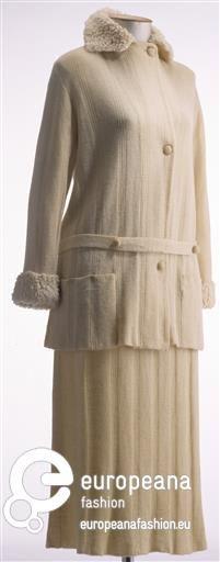 Damenkostüm aus cremefarbener Wolle Subnummer 1: Jacke in Rippenstrick, hochgeschlossen mit kleinem Spachtelkragen aus Lammpelzimitat, Knopfverschluss seitlich versetzt, Langarm mit Aufschlag aus Lammpelzimitat, gerade lose geschnitten, 2 aufgesetzte Taschen, Gürtel  Identifier M 13099/2 Temporal keyword um 1920