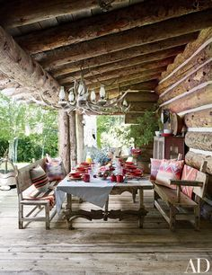A porch at Ralph Lauren's Colorado ranch is furnished with Mexican sabino-wood pieces, including a table made from a salvaged door and ox yokes; the tableware and linens are by Ralph Lauren Home. Rustic Outdoor Spaces, Outdoor Dining, Outdoor Rooms, Patio Dining, Outdoor Seating, Dining Table, Architectural Digest, Colorado Ranch, New York Homes