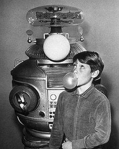 """Lost in Space. Guiones disparatados, extraterrestres y OVNIS de lo más excéntricos y un look sesentero muy cool. Los personajes más destacados son el malvado y cobarde Dr Smith, interpretado genialmente por Jonathan Harris y el robot, cuyo carácter cada vez es menos """"robótico""""."""