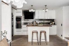 Fehér konyhabútor, konyhasziget, kopottas szürke és mozaik hátfal burkolat, acél és kő pultok