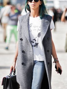Sleeveless blazer worn over a graphic tee and jeans