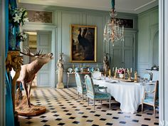In French filmmaker Jean-Louis Remilleux's Burgundy château, the north dining room is furnished with an 18th-century Italian chandelier, a Francis Barlow painting of a cassowary, and Louis XVI chairs.