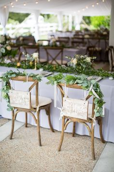 Rustic garland draped Mr. + Mrs. sweetheart chairs: http://www.stylemepretty.com/tennessee-weddings/nashville/2016/01/14/rustic-elegant-fall-wedding-at-cedarwood/ | Photography: Kelsey Combe - http://kelseycombe.com/#!/HOME