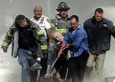 Rescue workers carry Fire Department Chaplain Father Mychal Judge from the rubble before the second tower of the World Trade Center collapse...
