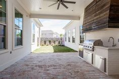 Open concept outdoor kitchen situated in a brick patio features an oversized reclaimed wood vent hood over a bbq built in island.