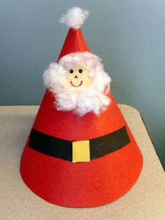 Santa Hat. Ages 3+. Cut a giant semi-circle out of 12 x 18 construction paper to make the hat shape. Then just add a circle face and belt from paper and some cotton batting.