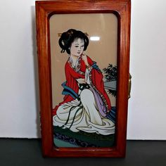 A small vintage, Asian, Geisha Girl, wood jewelry box with inside mirror on lid.  Shows a lovely picture of a geisha girl under glass on outside lid.