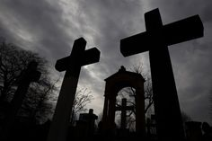 Stone crosses and gravestones are silhouetted against the sky at Invaliden cemetery in Berlin March 17, 2014. REUTERS/Tobias Schwarz