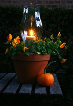 Place a small pot filled with pea gravel in the middle of a larger pot to hold a hurricane and candle. Fill larger pot space with soil and flowers. Great for a porch, patio or path!