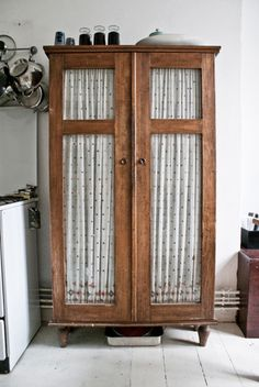 an old armoire used in the kitchen with adorable fabric to cover the glass panes to hide clutterbrilliant!