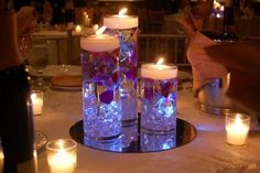Tall cylinder vases with votives, scattered single roses, bottom filled with crystals