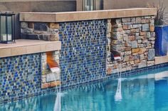 Iridescent glass tile with a natural stone and copper scuppers for a very unique architectural wall. #design #swimmingpool #pool #luxury #az #azluxury #azpool #design #modern #waterfeature #houzz #azhomes