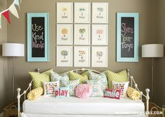 source: At Home in Arkansas    Girl's bedroom with vintage iron daybed, taupe walls paint color, turquoise blue framed chalkboard panels, framed vintage flashcards, green pillows, pink flower pillow and polished nickel floor lamps. decorpad.com