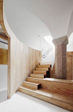 A stone and pine staircase leads down into a small space below this house in Barcelona.