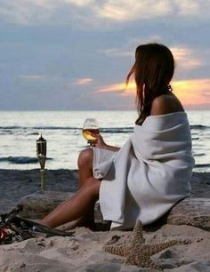 woman watching the sunset, drinking wine, beach