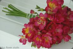 Freesia, wrapped with stems of variegated spider plant