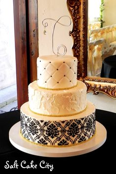 Black & Gold Wedding Cake - Gold & Black Damask Wedding Cake with lace appliques in the center tier. The whole cake is covered in marshmallow fondant and then I used black buttercream for the stenciled design and gold dragees around each tier. That took FOREVER! haha