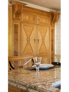 REFRIGERATOR ARMOIRE: An armoire with a natural-oak finish & corbel-topped pilasters conceals a structural column and two side-by-side Liebherr refrigerator-freezers. The island has a thick slab top of Arctic Cream granite finished with double-rolled edges. Two oak corbels with burl inlays support each of the four corners. ~ Kitchen Ideas: Two Kitchens in One | Traditional Home