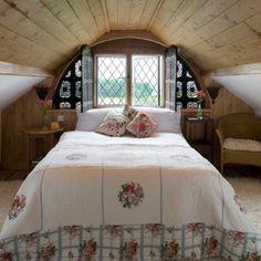 gemütliches schlafzimmer mit einem kleinen fenster
