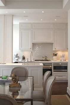 Greige kitchen cabinets with tile backsplash. Classic and neutral ...