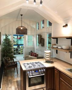 The kitchen features an L-shaped counter with eating bar and two stools, a four burner gas range, refrigerator, microwave, and stainless steel sink.