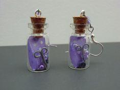Boucles d'oreilles flacon en verre contenant accessoires de couture mauve : ruban , ciseaux , perles et boutons .