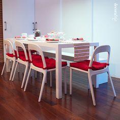 Mesa branca com assentos coloridos