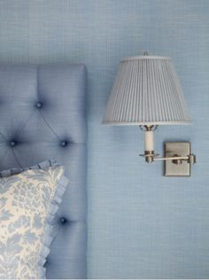 blue on blue...  Grasscloth walls, linen/silk bedhead, pleated silk shade on burnished nickel swing-arm lamp.