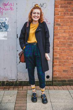immagine-anni-80-ragazza-pantaloni-scozzesi-blu-maglia-ocra-calzini-colorati-borsa-tracolla-pelle-marrone-capelli-rossi-mossi