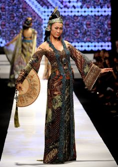 A model showcases designs on the runway by Anne Avantie