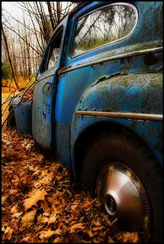 Blue car with fall leaves