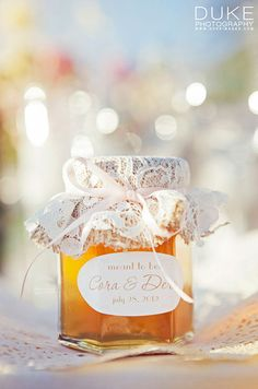 Glass honey jars wrapped in burlap and lace serve as delicious and adorable wedding favors for guests.