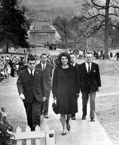 Jackie visits her husband's grave in 1964, as Clint Hill, her secret service agent follows close behind. He is the agent who was seen climbing onto the Presidential limo when Jackie tried to get away from the horror she had just witnessed. He was able to push her back into her seat and he climbed on top for protection on the way to Parkland hospital.