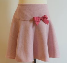 Pink wool skirt Description: pretty circular style giving it a lovely fullness, matching grosgrain ribbon bow, concealed zip at side, adjustable elastic waist Sizes: available in 3y, 4y, 5y, 7y From £32