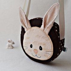 Taštička s králíčkem Taštičkaušitá z bavlny a syntetiky.Vše je podlepenéronofixem pro pevnější tvar.Aplikace podlepená vlizelínem a strjově přišité.Popruh nastavitelný.Možnost šetrného praní na 30C°  Výška:15cm šíře:16cm