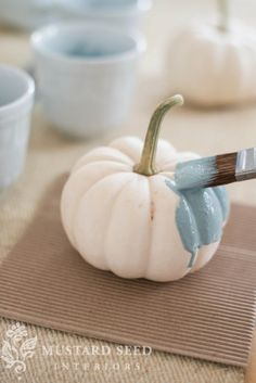 "Making ""blue"" pumpkins by painting mini white pumpkins with milk paint + white wax..."