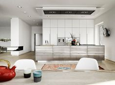 Designed by Kobenhavn Design, this open kitchen has floor-to-ceiling white cabinets with built-in appliances, along with a massive stainless steel covered island that contains the cooktop and sink.