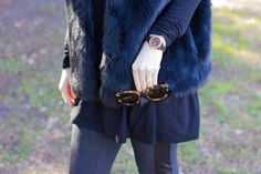 black fur vest, black piko tunic, karen walker tortoise sunglasses, j crew tuxedo pant, black crowd booties
