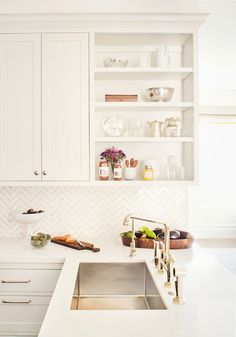 Kitchen cabinets with no doors over off-white base cabinets paired with white quartz countertops and white chevron tile backsplash over kitchen peninsula with sink.