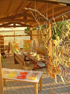 Outdoor art space with hanging weaves, a communal table, and art easels.