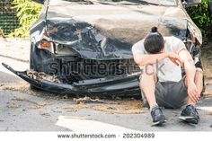 Desperate man crying on his old damaged car after a crash accident